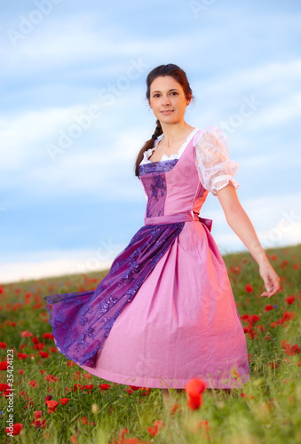 Young woman with dirndl dress in poppy field