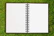 White notebook on grass field texture.