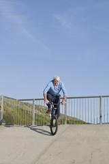 Senior man on bicycle riding down skate park
