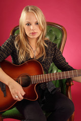Female guitarist sitting on leather chair