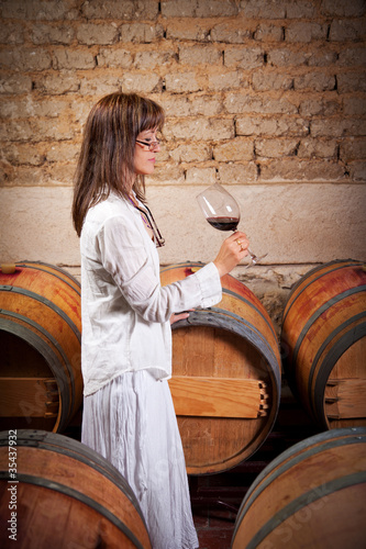woman tasting red wine in an old cellar