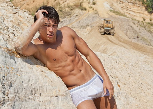 Sexy wet muscle young boy lean against sands