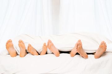 Familie unter der Bettdecke
