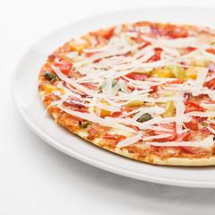 Pizza mit Parmesan auf weissem Teller auf weisser Tischdecke
