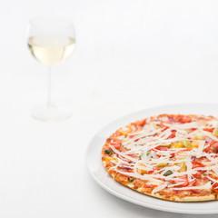 Pizza mit Weißwein auf weissem Porzellan und weisser Tischdecke