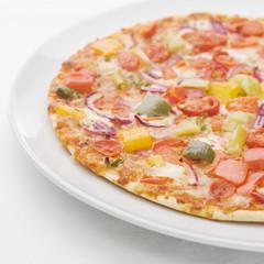 Gemüsepizza auf weissem Teller auf weisser Tischdecke