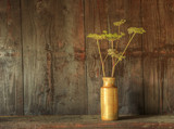 Retro style still life of dried flowers in vase against worn woo