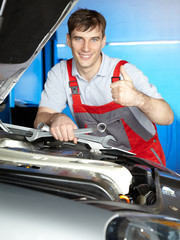 Satisfied master mechanic shows thump up for a good job