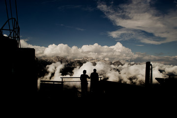 Couple on top of the mountain watching the clouds