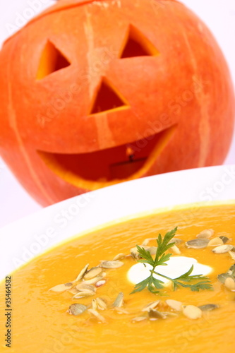 Pumpkin soup with Jack-o'-lantern in the background