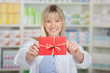 lächelnde apothekerin mit gutschein