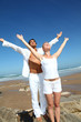 Couple doing yoga exercises on the beach