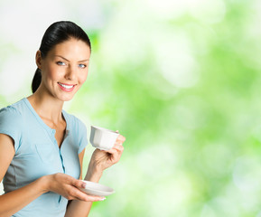 Young woman drinking coffee, outdoors, copyspace