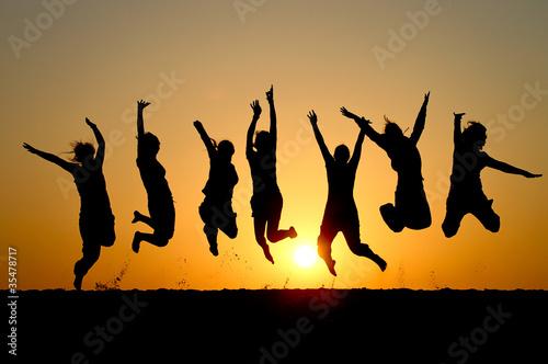 Zdjęcia na płótnie, fototapety na wymiar, obrazy na ścianę : silhouette of friends jumping in sunset