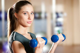 Beautiful sport woman doing exercise with dumbbell
