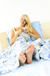 Woman sitting in bed with coffee cup