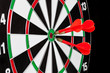 Darts hitting the bullseye on a dartboard