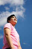 Young man in a pink shirt against the blue sky