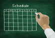 Hand writing schedule on chalkboard