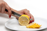 Women cut lemon on a white plate