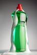 botella llena de detergente en fondo gris cubierta de espuma