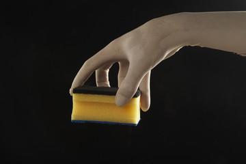 mano con guante de latex sujetando un estropajo en fondo aislado
