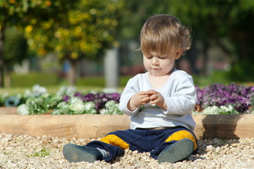 Little boy sits and plays in the park