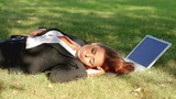 Beautiful business woman relaxing on grass with laptop