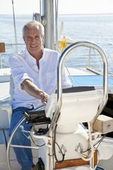 Happy Senior Man At The Wheel of a Sail Boat