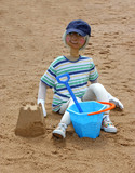 A Scarecrow Figure of a Youngster Playing in the Sand. poster