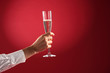 female hand with a glass of champagne on red background