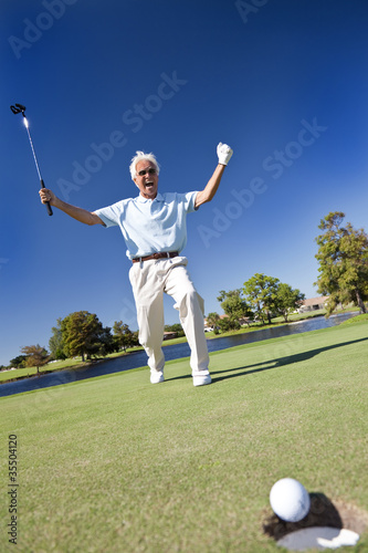 Senior Man Playing Golf Celebrating On Putting Green