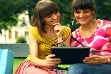 Happy friends with tablet computer in the park, steadycam shot