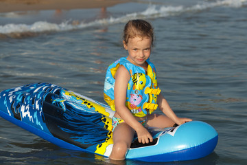 Child on an inflatable mattress in the sea.