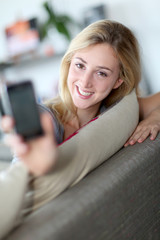 Smilng woman showing smartphone towards camera