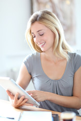 Young woman working at home with touchpad