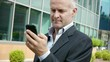 man smiling near office building with cell phone