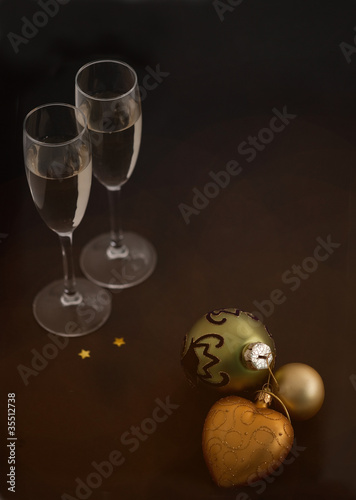 Christmas balls and glasses of champagne on black background