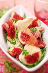 Fresh salad with figs, prosciutto and goat cheese, soft focus