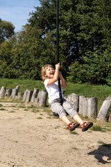 Fun in the park. Girl pulls down the hill on a rope