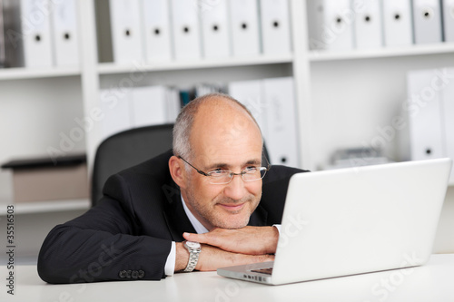entspannter geschäftsmann liest am laptop