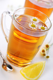 cup of herbal tea with chamomile flowers and lemon