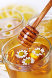cup of herbal tea with chamomile flowers and wooden stick honey