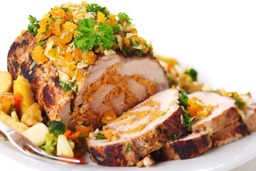 Stuffed pork roast with dried apricots and nuts on white backgro