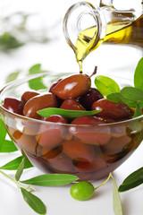 Olive oil poured from an original bottle into black olive