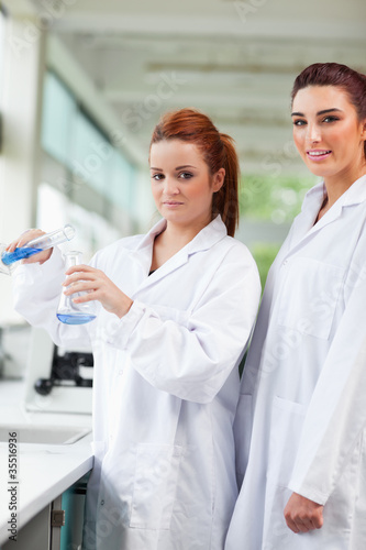 Portrait of scientists pouring blue liquid in an Erlenmeyer flas