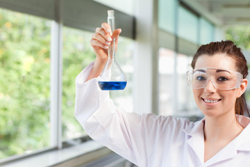 Female science student holding a blue liquid