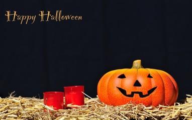 Calabaza con dos velas y Feliz Halloween.