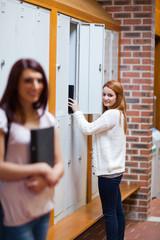 Portrait of a student picking her binder in her locker