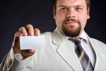 A man shows a business card. Focus on hand.